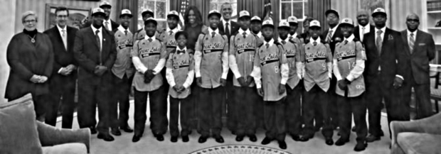 President Barack Obama and first lady Michelle Obama pose with the Jackie Robinson West All Stars Little Baseball League in the Oval Office of the White House in Washington, D.C., Nov. 6, 2014. (YURI GRIPAS/AFP/Getty Images)